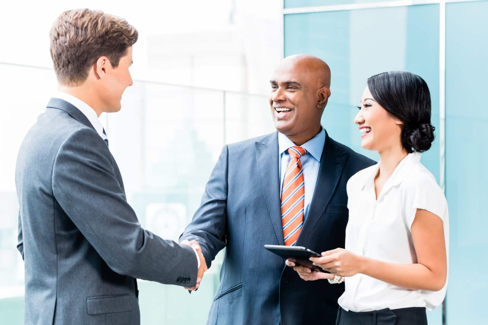 Businessman Shaking Hands With Younger Businessman While Woman Watches