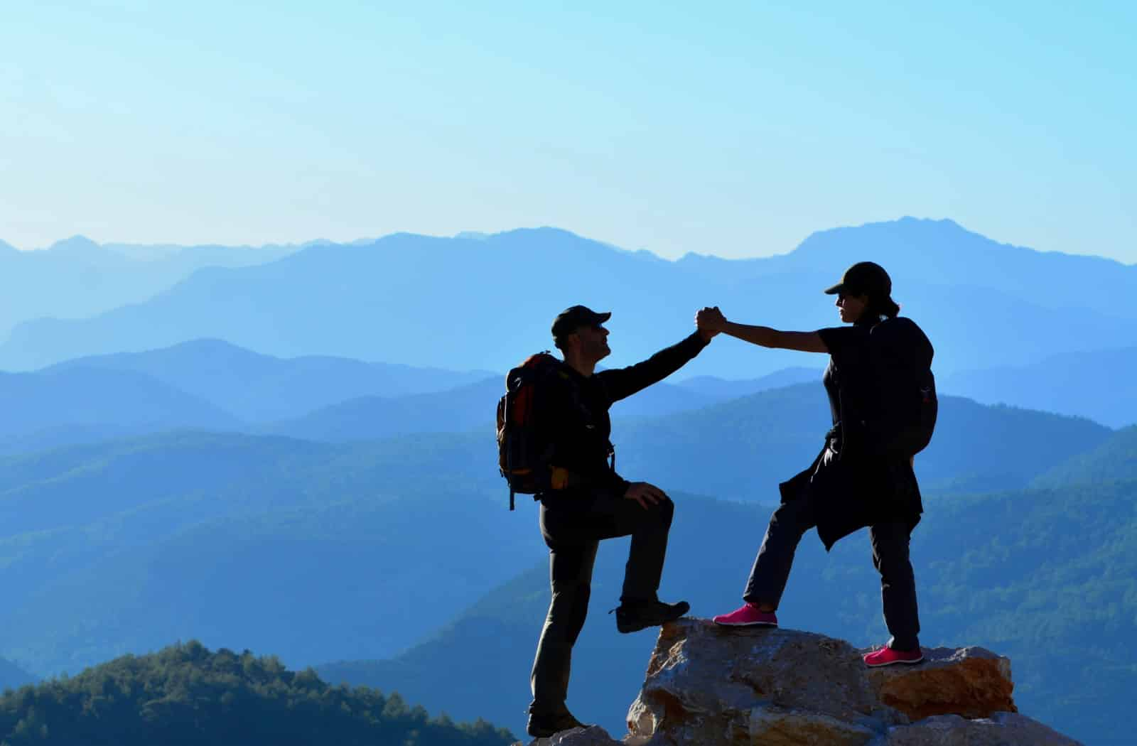 Hikers Holding Hands On High Rock With Mountain Background